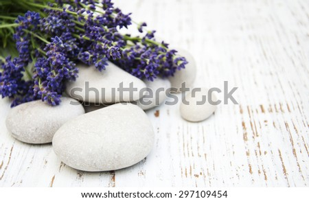 Lavender and massage stones on a old wooden background - stock photo