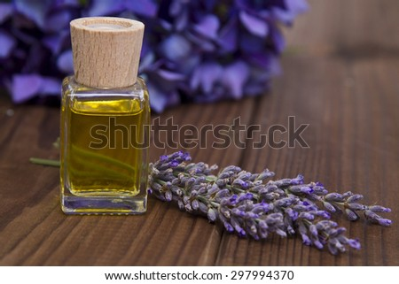 lavender and oil on wooden background - stock photo