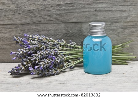 Lavender and some hygiene items made of lavender on an old wooden shelf. - stock photo