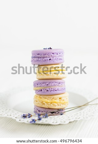 Lavender and vanilla macarons in stack on white lace plate. Selective focus