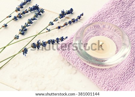 Lavender aromatherapy. Tea aromatic candle on purple towel, dried lavender herbs. Toned.  - stock photo