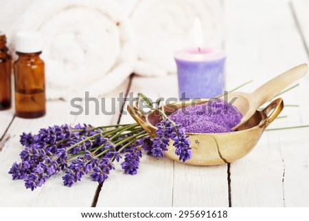lavender flowers, bath salt, massage oil, scented candle and towels on rustic white background, high key image - stock photo