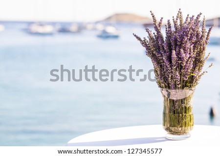 Lavender flowers in a glass vase on a table by the ocean.