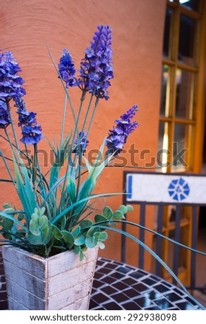 Lavender flowers in ceramic pot on table with chair  - stock photo