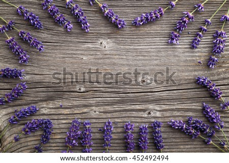Lavender flowers on a wooden background. Floral border or frame with lavender. - stock photo