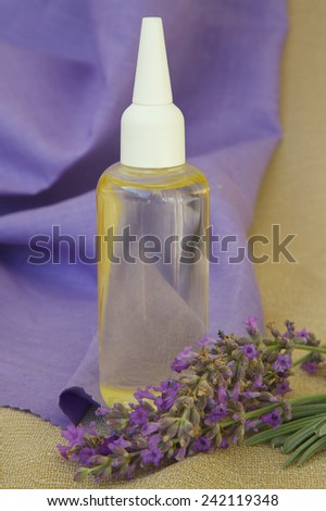 Lavender hair oil. Lavender twigs in the background. - stock photo