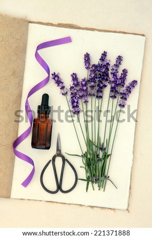 Lavender herb flower stems, aromatherapy bottle, scissors and purple ribbon on a hemp paper notebook over mottled cream background. - stock photo