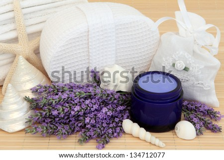 Lavender herb flowers, white linen bag with moisturiser and bathroom accessories.