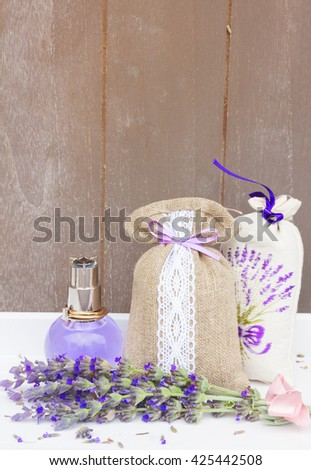 Lavender herbal  water, fresh flowers and dry in pouch, copy space on gray wooden planks - stock photo