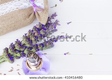 Lavender herbal water in a glass bottle with fresh and dry flowers in pouch, copy space on white wooden table - stock photo