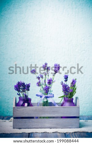 Lavender in bottles, decor provance style, wooden box on crochet tablecloth - stock photo