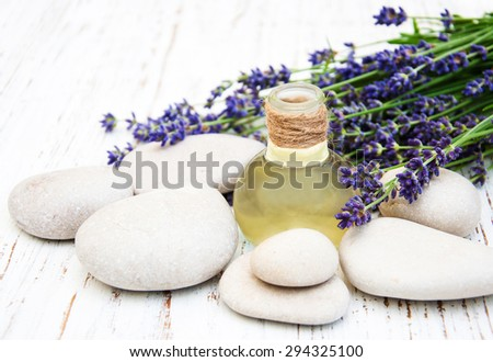 Lavender, oil and massage stones on a old wooden background - stock photo