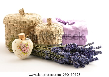 Lavender oil and perfume in a ceramic bottle  on a white background of fresh flowers and  baskets - stock photo