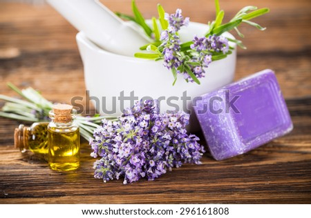 Lavender oil, herbal soap and fresh lavender flowers on wooden background. Wellness still-life. - stock photo