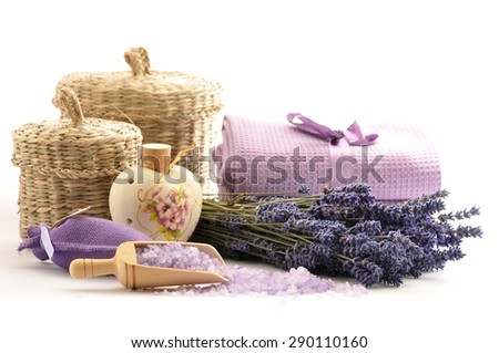 Lavender oil in a ceramic bottle on a white background of fresh flowers and  baskets