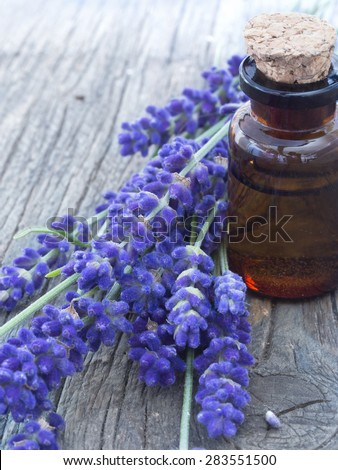 lavender oil in the glass bottle with fresh flowers on the wooden table