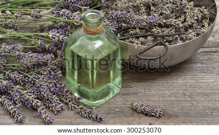Lavender oil with fresh flowers and scissors on wooden background. Vintage style still life - stock photo