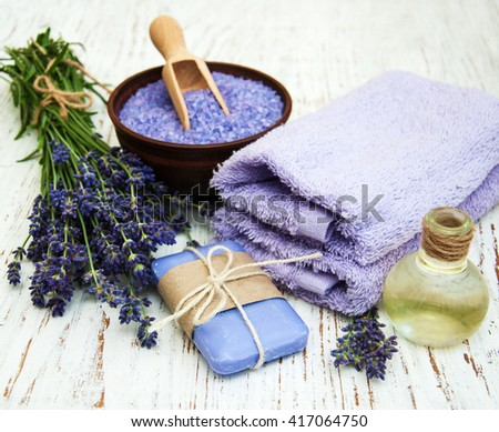 Lavender, sea salt and massage oil on a wooden background - stock photo