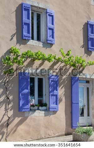 Lavender shutters on an old house facade in Provence, France. - stock photo