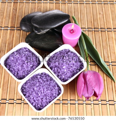 Lavender spa salt, spa stones, a candle and a tulip flower