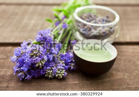 Lavender tea in a clay bowl on a wooden table - stock photo