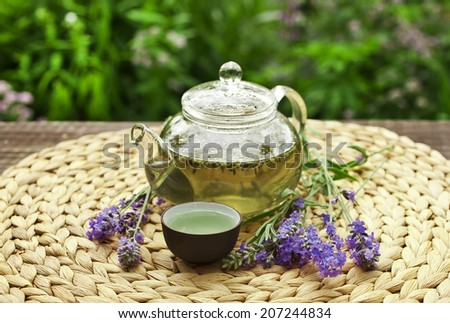 Lavender tea in a glass teapot on a table in the garden - stock photo
