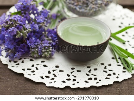 Lavender tea in a small clay bowl and lavender flowers - stock photo