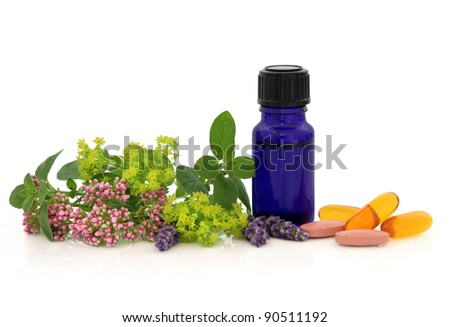 Lavender, valerian and ladies mantle herb flower heads with marjoram leaf sprigs, aromatherapy bottle and vitamin pills isolated over white background. - stock photo
