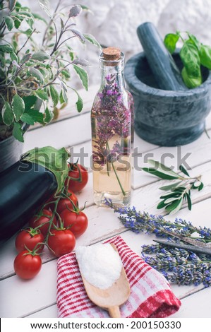 Lavender vinegar in bottle, tomato, egg-plant and sage plant on white kitchen table - stock photo