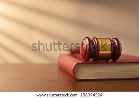 Law book and wooden judges gavel on a wooden table top in a shaft of sunlight with rayed shadow effect, conceptual image of law enforcement with copyspace - stock photo