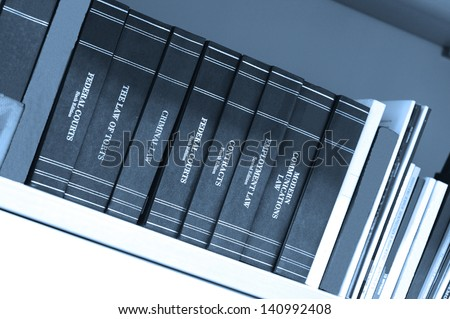 Law books on a bookshelf in a library, blue tone - stock photo