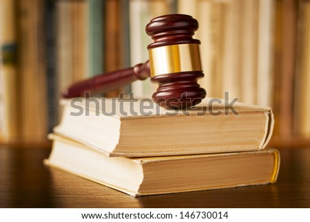 Law books with a wood and brass judges gavel resting on top on a wooden desk, closeup view with shallow dof
