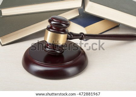 Law concept - Book with wooden judges gavel on table in a courtroom or enforcement office.