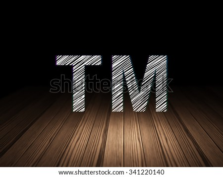 Law concept: Glowing Trademark icon in grunge dark room with Wooden Floor, black background - stock photo