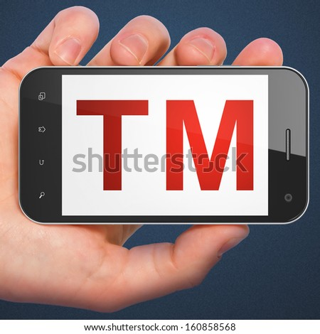 Law concept: hand holding smartphone with Trademark on display. Mobile smart phone on Blue background, 3d render - stock photo