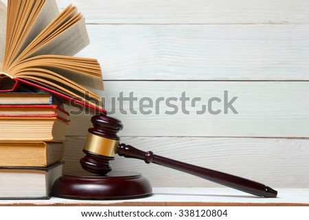 Law concept - Open law book with a wooden judges gavel on table in a courtroom or law enforcement office. Copy space for text - stock photo