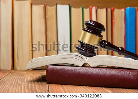 Law concept - Open law book with a wooden judges gavel on table in a courtroom or law enforcement office.