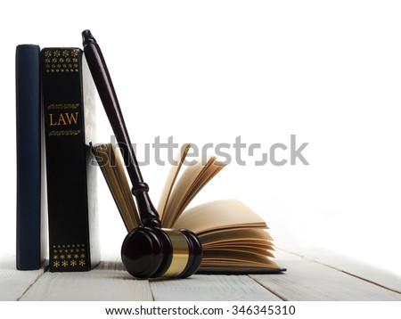 Law concept - Open law book with a wooden judges gavel on table in a courtroom or law enforcement office isolated on white background. Copy space for text - stock photo