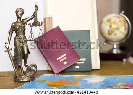 Law concept, statue, magnifying glass, passport and world map. Travel - stock photo