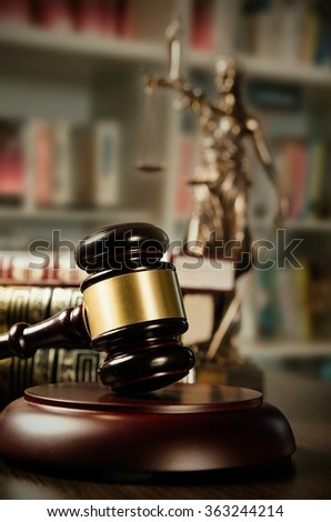 Law concept with gavel and Themis in background. Composition in court library - stock photo