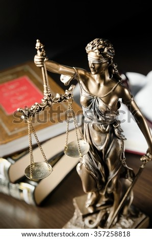 Law concept with Themis and books in background. Composition in court library - stock photo