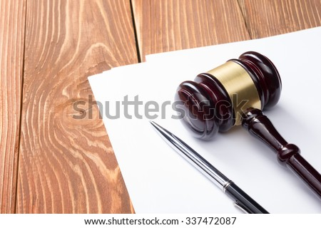 Law concept - Wooden judges gavel and pen on blank sheet of paper on table in a courtroom or law enforcement office. Top view