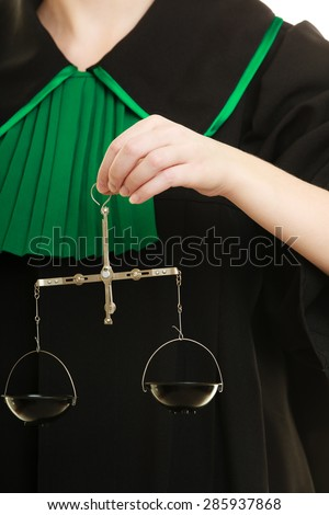 Law court concept. Woman lawyer attorney wearing classic polish black green gown holds scales. Femida - symbol sign of justice closeup - stock photo