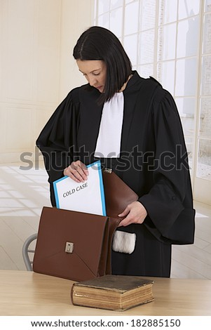 Law court or justice concept. Young woman lawyer attorney wearing classic  french black white gown stowing a cold case  file folder in her briefcase - stock photo