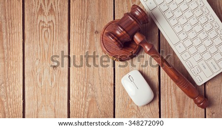 Law gavel and keyboard on wooden background. Online law enforcement concept. View from above - stock photo