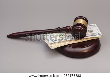 Law gavel on a stack of dollars isolated on gray background - stock photo