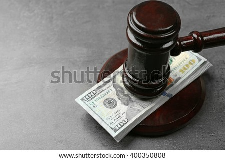 Law gavel with dollars on grey background, closeup - stock photo