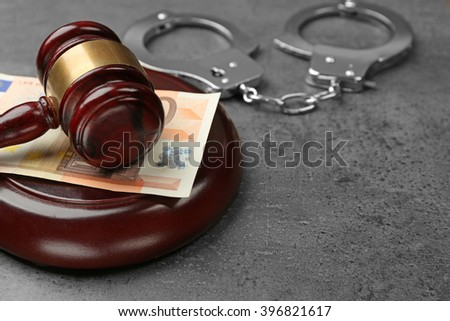 Law gavel with euro and handcuffs on grey background, closeup