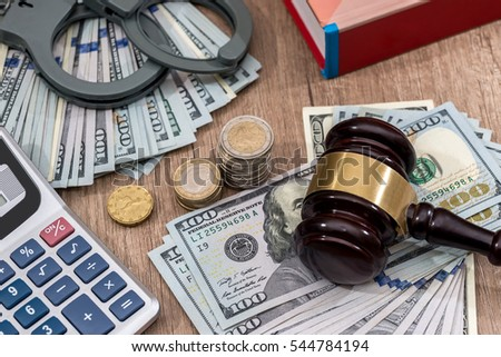 Law gavel with handcuffs, dollars and books as background, close up.