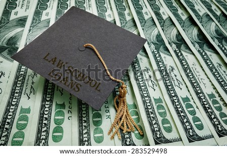 Law School Loans graduation cap on assorted hundred dollar bills - student loan concept                                - stock photo